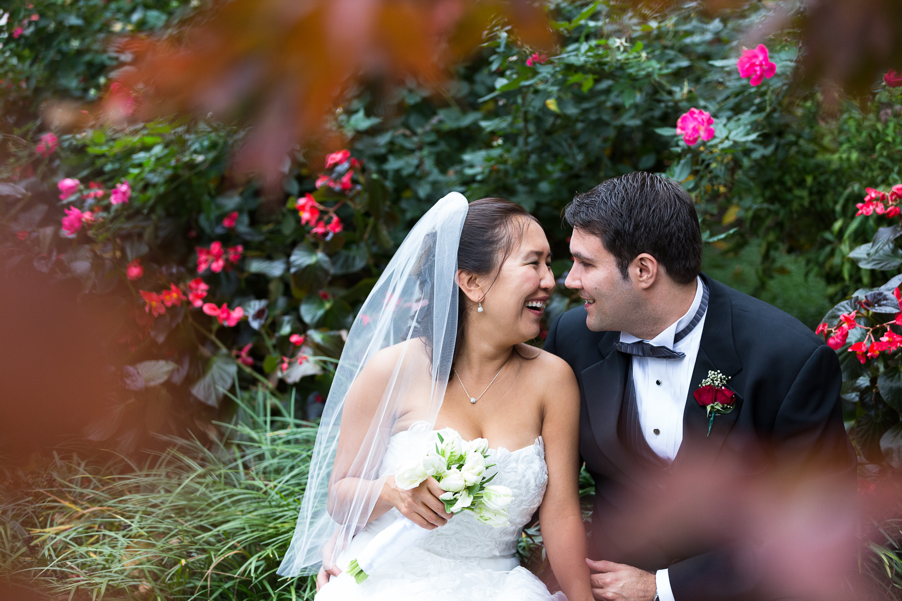 bride-and-groom-snuggle-among-flowers