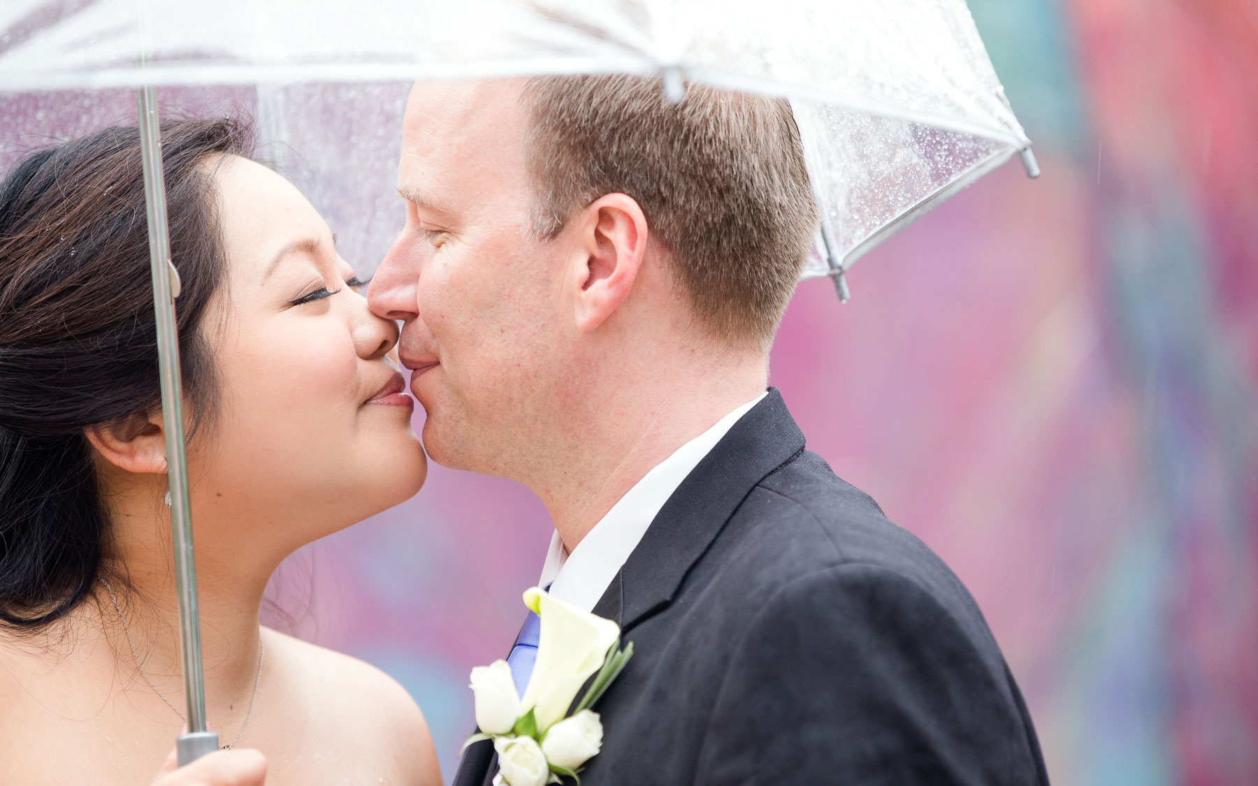 bride-and-groom-kiss-under-umbrella-in-rain