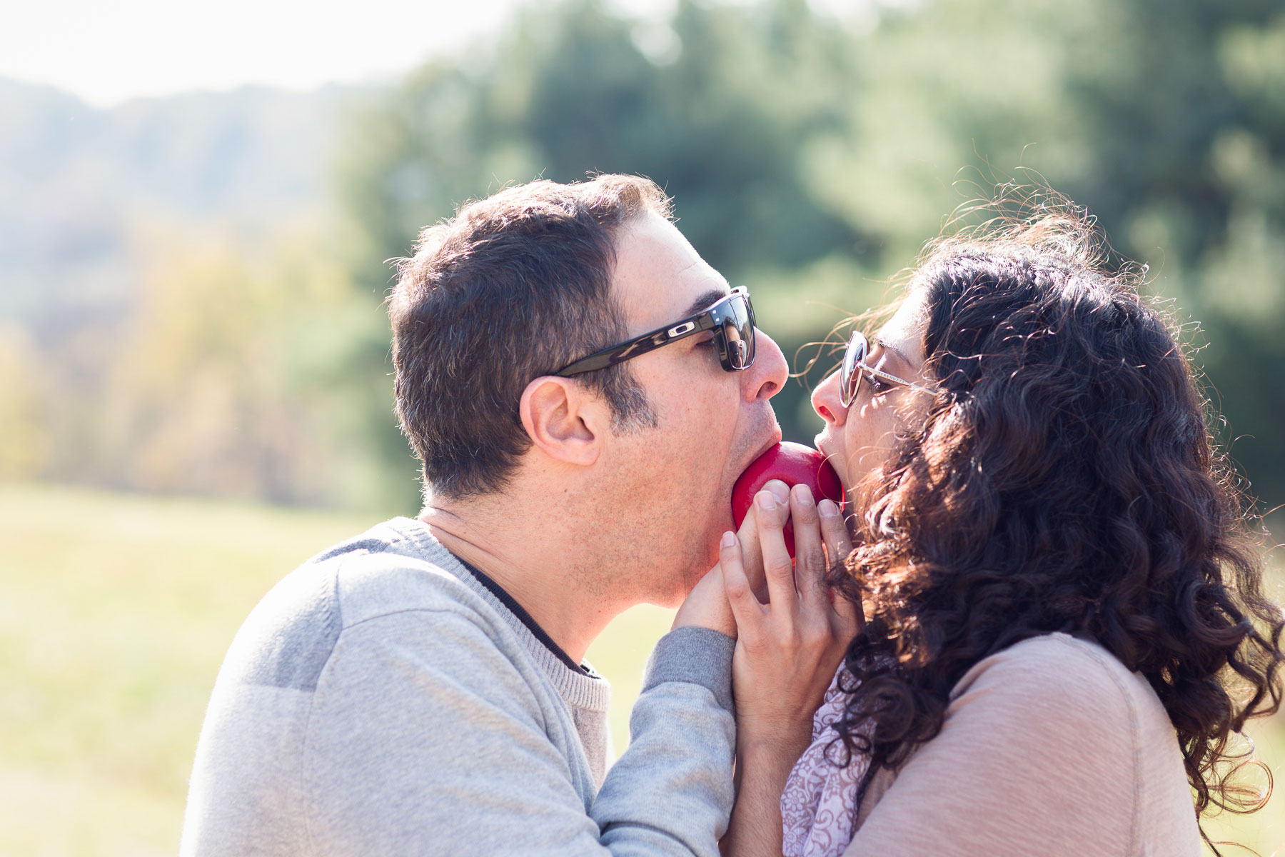 engagement-portrait-apple-orchard-couple-eats-apple-together
