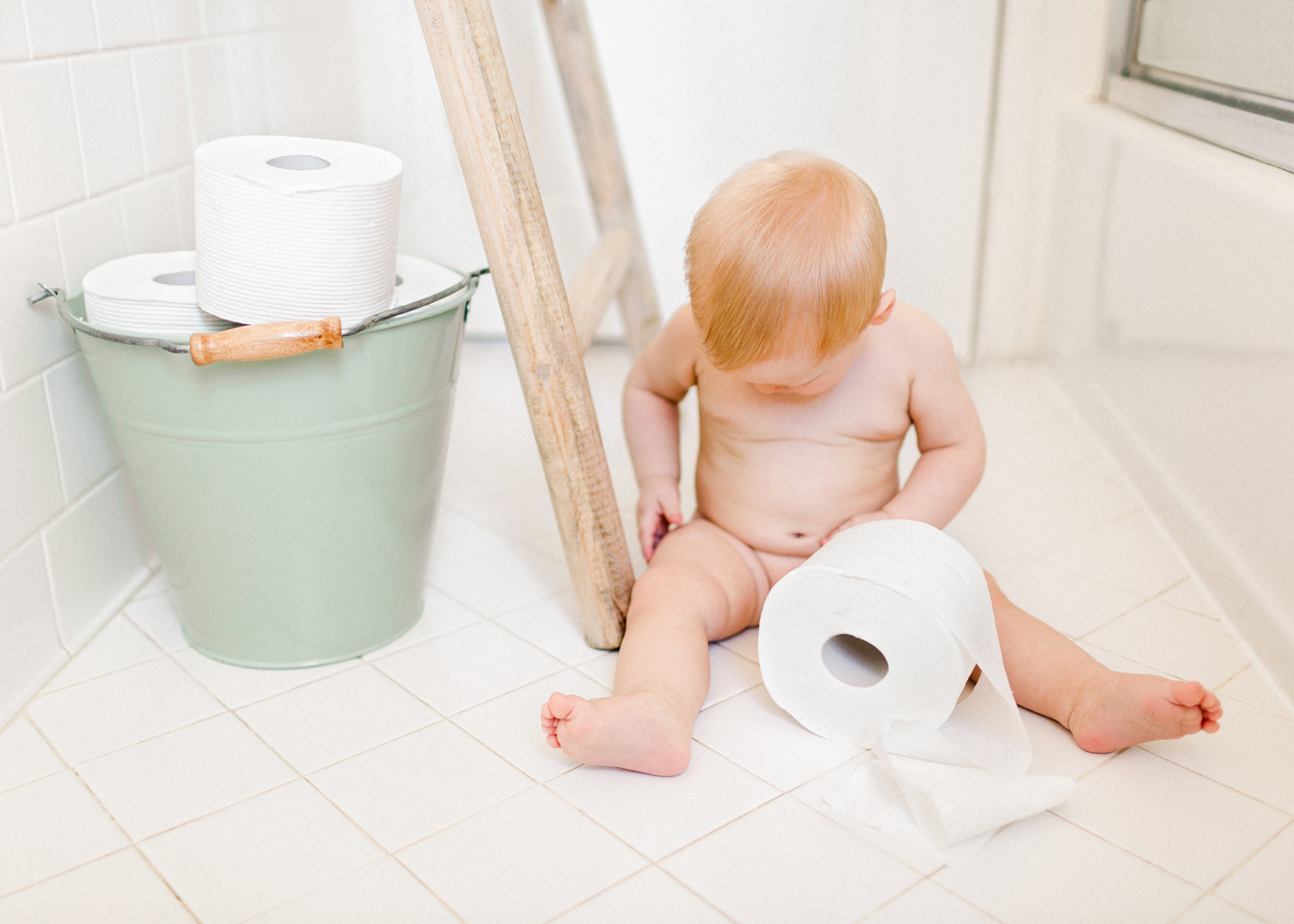 baby-boy-plays-with-toilet-paper-in-bathroom